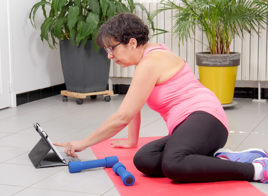 Middle-aged woman doing fitness exercises with tablet, at home