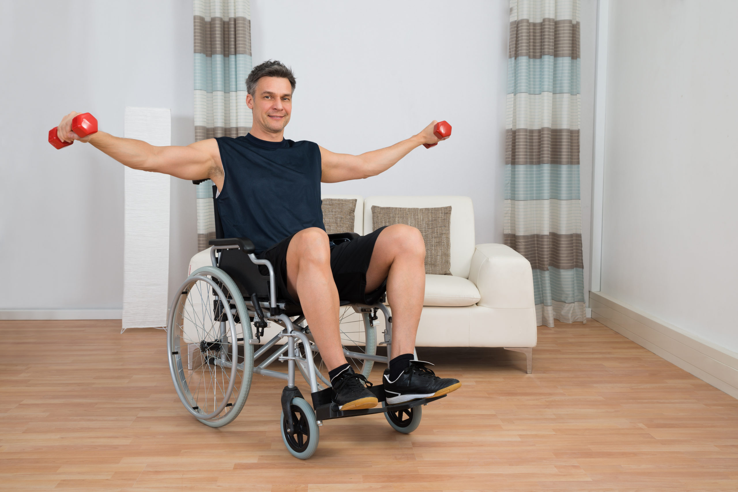 Handicapped Man On Wheelchair Working Out With Dumbbell At Home