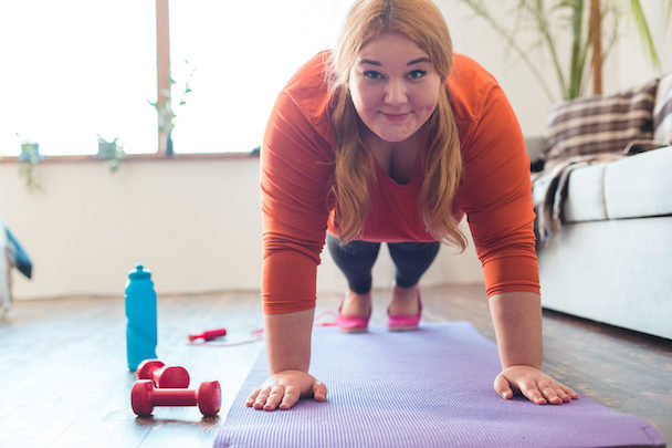 Chubby woman sport at home standing on arms on yoga mat looking camera smiling happy